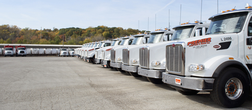 A lineup of For Sale Roll Off and Garbage Trucks